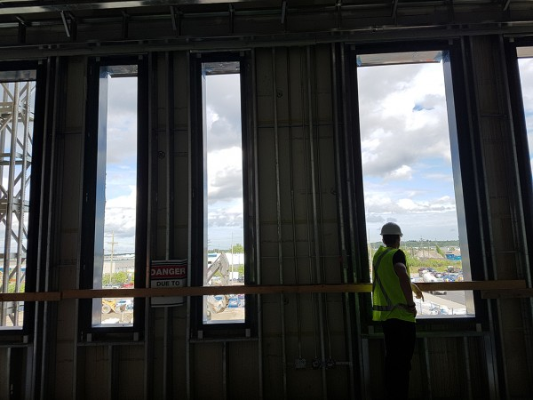 A staff member pauses to look out of the Ingenium Centre's east façade, towards the parking lot.