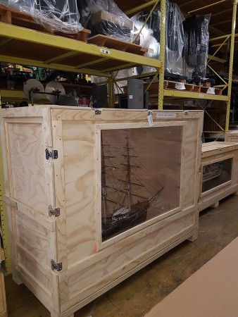 A ship model in an open-style storage crate.