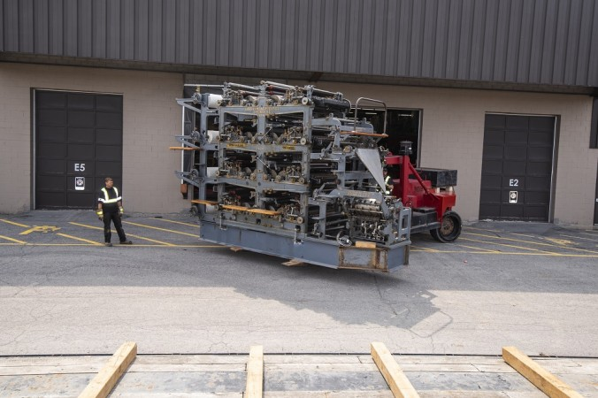 A 35 metric ton forklift raises the Goss printing press onto a flatbed truck.