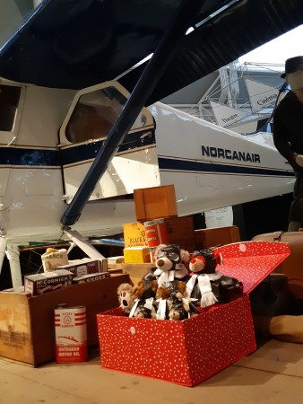 A red box filled with teddy bears dressed as pilots sits next to an aircraft in a museum.