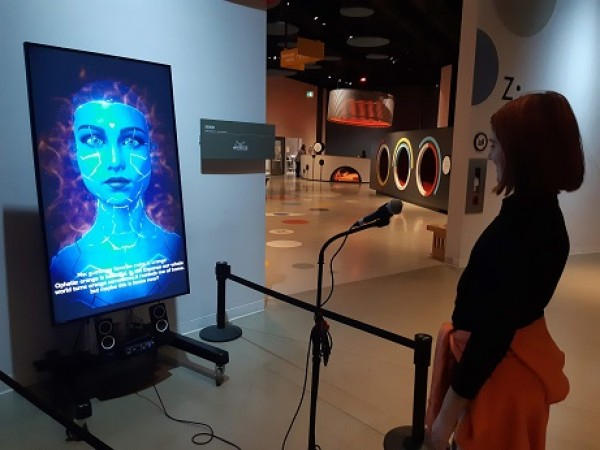 A young girl stands in front of a microphone, looking at a large screen with a blue avatar of a woman's face.