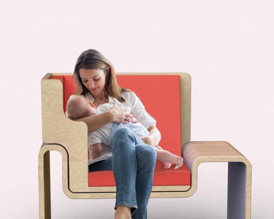 A young woman breastfeeds an infant on a modern-looking chair with an orange seat.