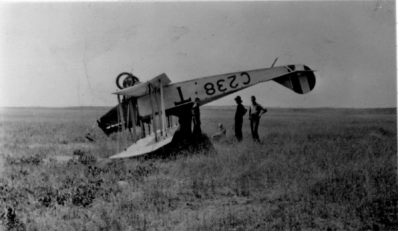 Image is a black-and-white photograph showing a Curtiss JN-4 biplane crashed in a field. The airplane is completely upside down.