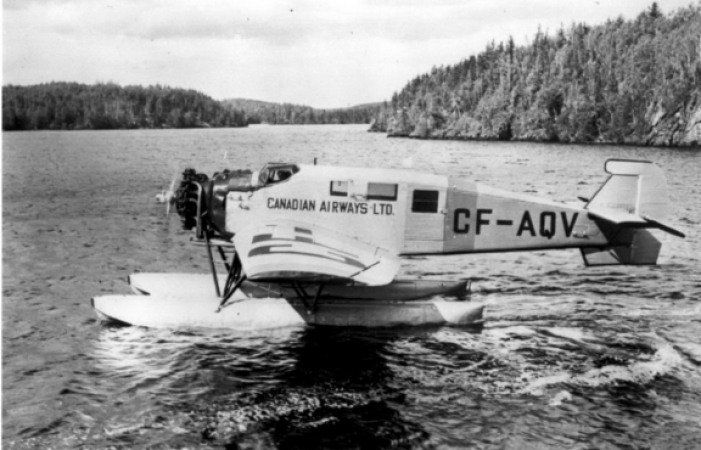 "Image is a black-and-white photograph showing a seaplane in a lake with shore or islands covered in trees in the background. ""Canadian Airways Ltd"" and registration number ""CF-AQV"" shows on the side of the aircraft."