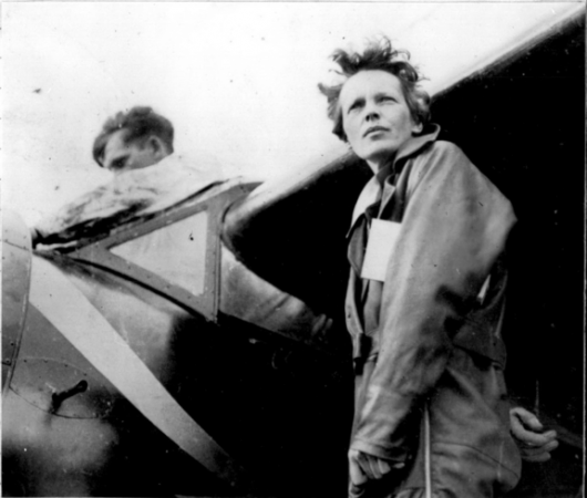 Black and white photograph of pilot Amelia Earhart standing under the wing of her aircraft as a man works on something in the cockpit.