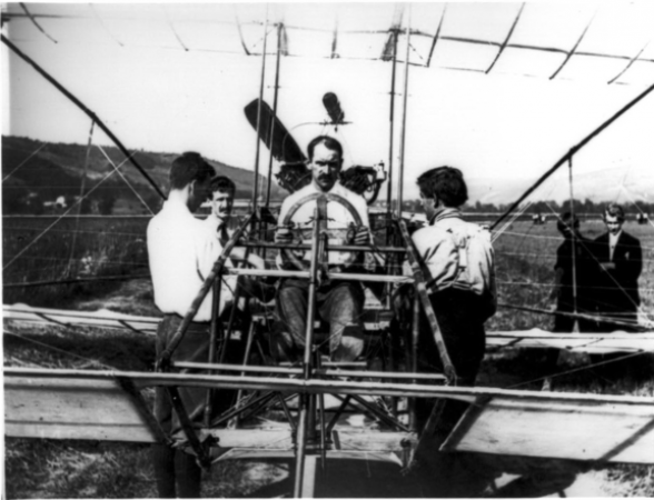 Black and white photograph showing a man sitting at the controls of an early aircraft with an open frame.  His colleagues from the Aerial Experiment Association stand around him.