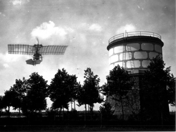 Black and white photograph showing a Santos-Dumont Demoiselle, an early aircraft with an open frame, in the sky above some trees and near a water tower.