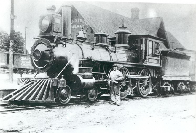 Image is a black-and-white photograph showing a steam locomotive in front of a station building. Grand Trunk is visible on the side of the station. A workman with an oil can is posing in front of wheels of the locomotive.
