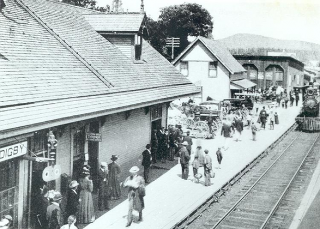 Image is a black-and-white photograph showing people waiting on the platform of the train station in Digby, Nova Scotia. A steam locomotive is approaching on the tracks on the right side of the photograph.