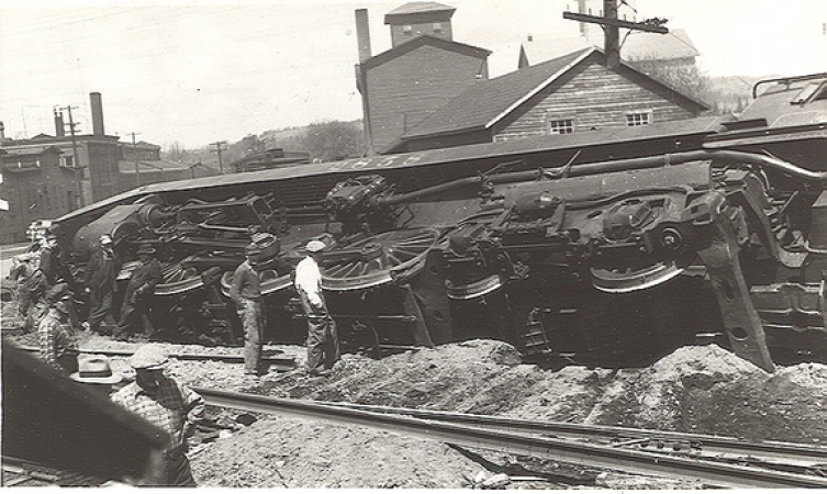 Image is a black-and-white photograph showing a steam locomotive that has derailed and is lying on its side. Men in the foreground stand looking at the wreck.