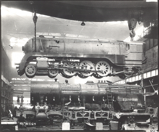 Image is a black-and-white photograph of a steam locomotive being built. It shows a locomotive suspended in the air with parts on the ground.