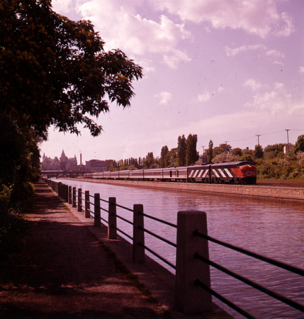 Image is a colour photograph showing a freight train with a red CN diesel locomotive on the rail line beside the Rideau Canal, in Ottawa.