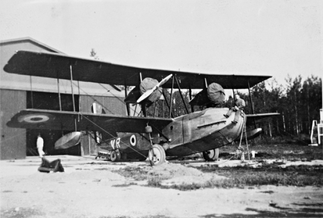 Image is a black-and-white photograph showing a twin-engine Vickers Vancouver II bi-plane in front of a hanger. A man is sitting on the nose of the aircraft.