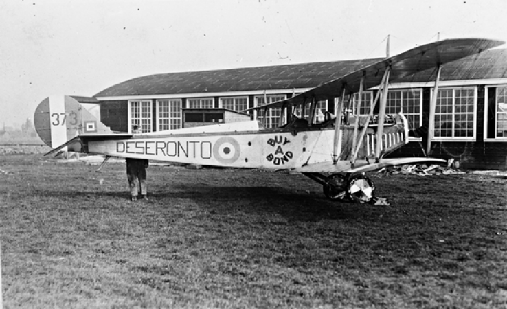 "Image is a black-and-white photograph showing a side view of a Curtiss JN-4 aircraft in an airfield. ""Deseronto"" and ""buy a bond"" are written on the side of the plane."