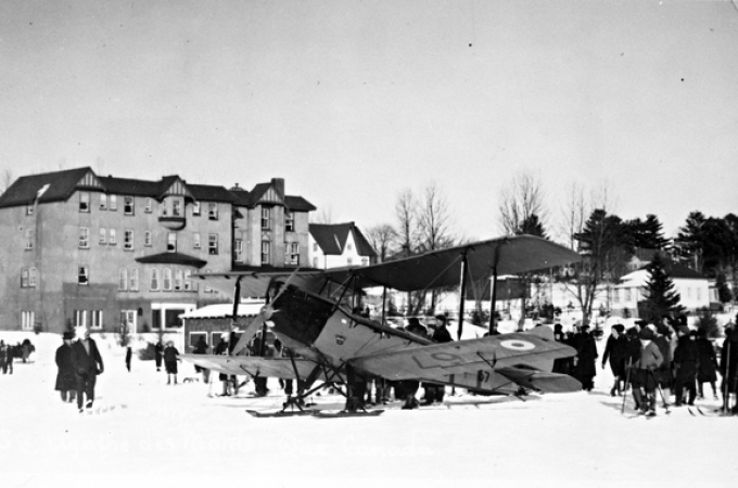 Image is a black-and-white photograph of a biplane aircraft in a snowy field in front of a large hotel. People surround the aircraft, some of them are on skis. The aircraft is a de Havilland D.H.60 Moth and also has skis.