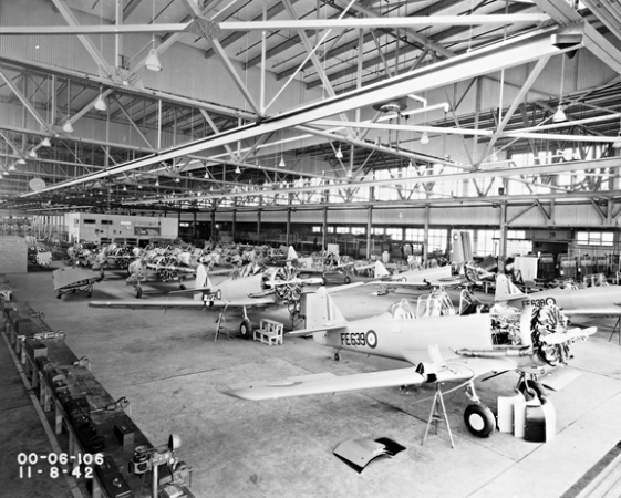 Image is a black-and-white photograph showing aircraft being assembled on the Noorduyn factory floor. Aircraft on the floor are in a line and are still missing parts, such as wings.