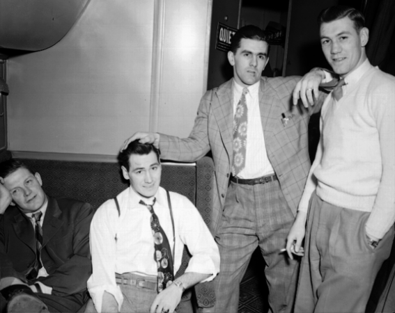 Image is a black-and-white photograph showing players from the Montreal Canadiens sitting or standing in a train car. Maurice Richard has his hand resting on one sitting player's head and his elbow up on the shoulder of the player standing beside him.