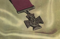 This photo shows the cover of a booklet with Victoria Cross in the center on a background of white silk and the letter V C in red at the bottom.