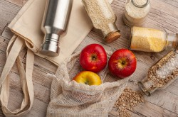 Red apples and various grains are pictured in reusable containers and cloth bags.