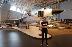 Victor Deng the student intern standing in front of the Avro Arrow and the CF-18