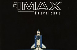 "A white and blue space shuttle leaves the Earth's atmosphere and is pointing upwards to the words ""The IMAX Experience.""  The image background is black, the text is white, and we can see a blue ocean with some white clouds in the Earth at the bottom of the picture."