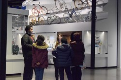 A group of teenagers and one coordinator gather in a circle to sort out their ideas and problem solve. Behind them is a showcase of the different kinds of bikes there have been through time.