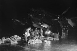 A black-and-white image depicts a group of men standing underneath a Royal Air Force Avro Lancaster; they are loading cloth supply bags into the bomb bay. Wikimedia Commons
