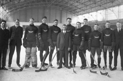 A black-and-white image of team of young hockey players, posing on the ice with their hockey sticks.
