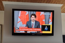 In a living room with a straight-on view of the Prime Minister of Canada on a television.