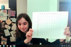 Image of a video chat taken from a computer screen. A girl appears onscreen, smiling and holding up a grid covered with coloured markings.
