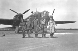 Five men, suited in their flight gear, walk towards the camera with a bomber airplane, facing forward and to the right, in the background.