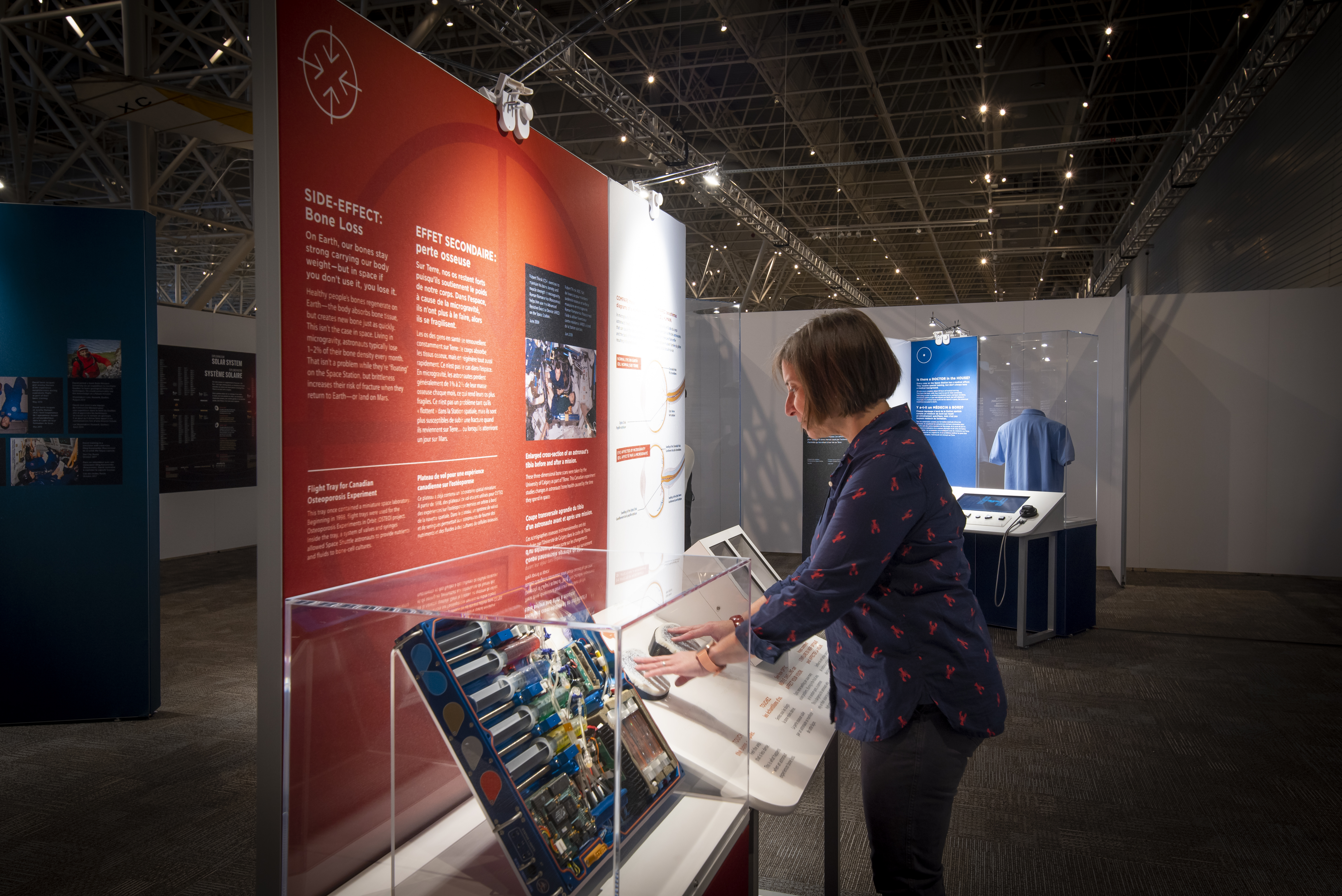 A woman stands in front of an exhibition panel inside the Canada Aviation and Space Museum.