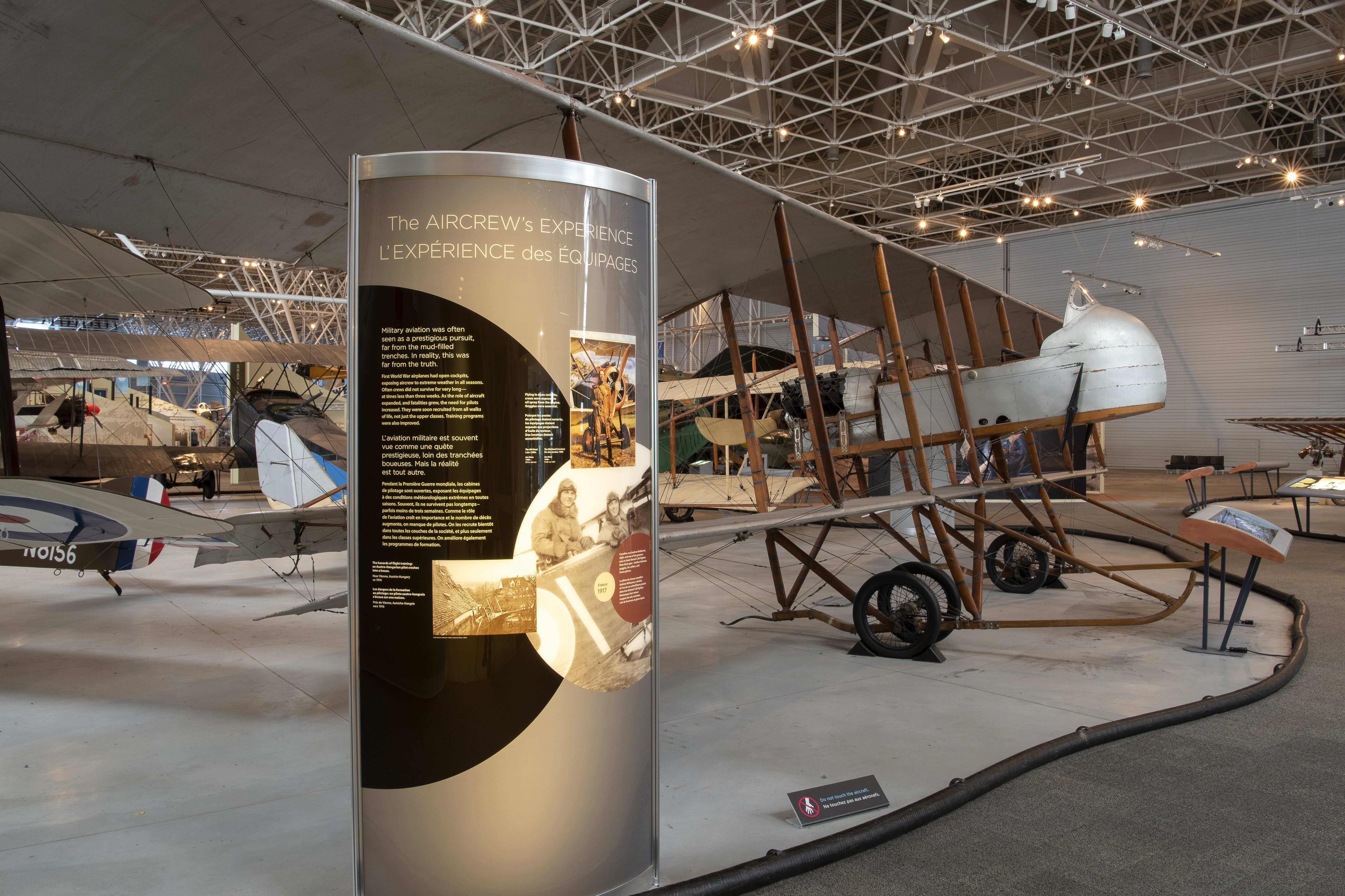 A sleek-looking panel stands in the foreground; in the background several aircraft are visible on the floor of the Canada Aviation and Space Museum.