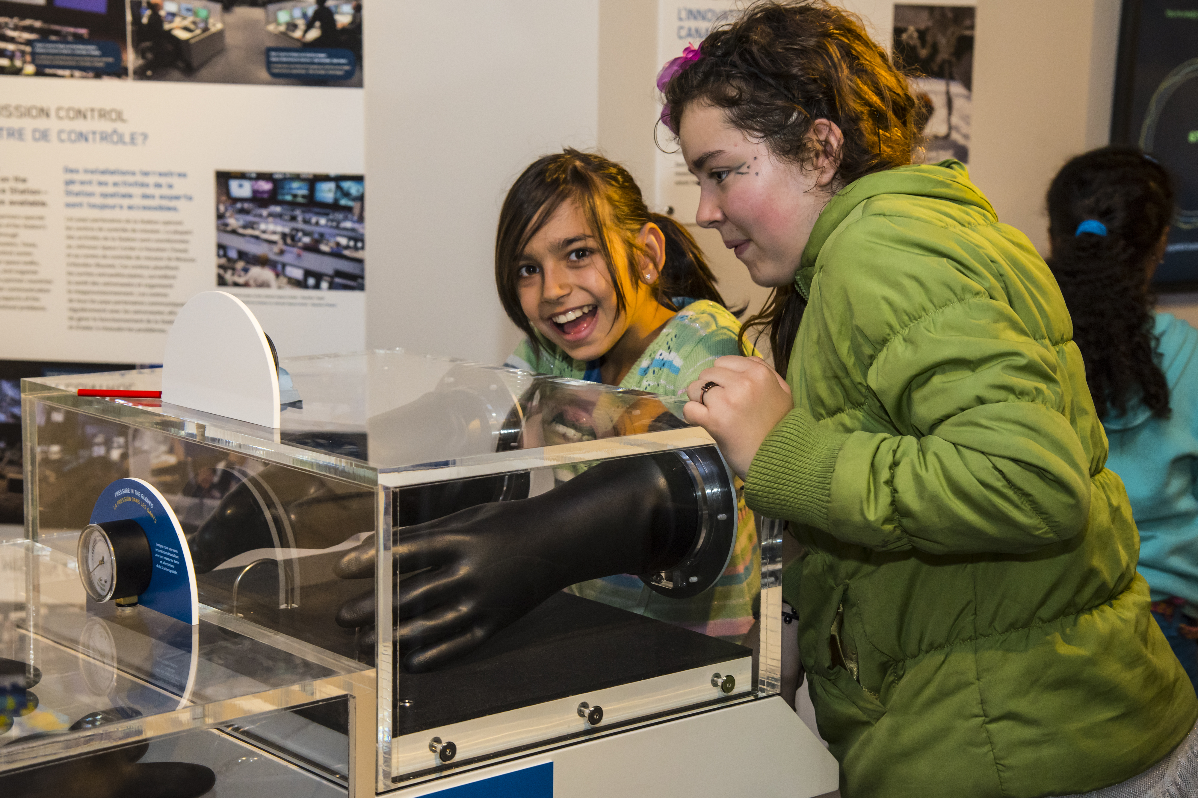 Two young girls stand next to a glass case in a museum; one girl is inserting her hand into a black pressurized glove inside the case.