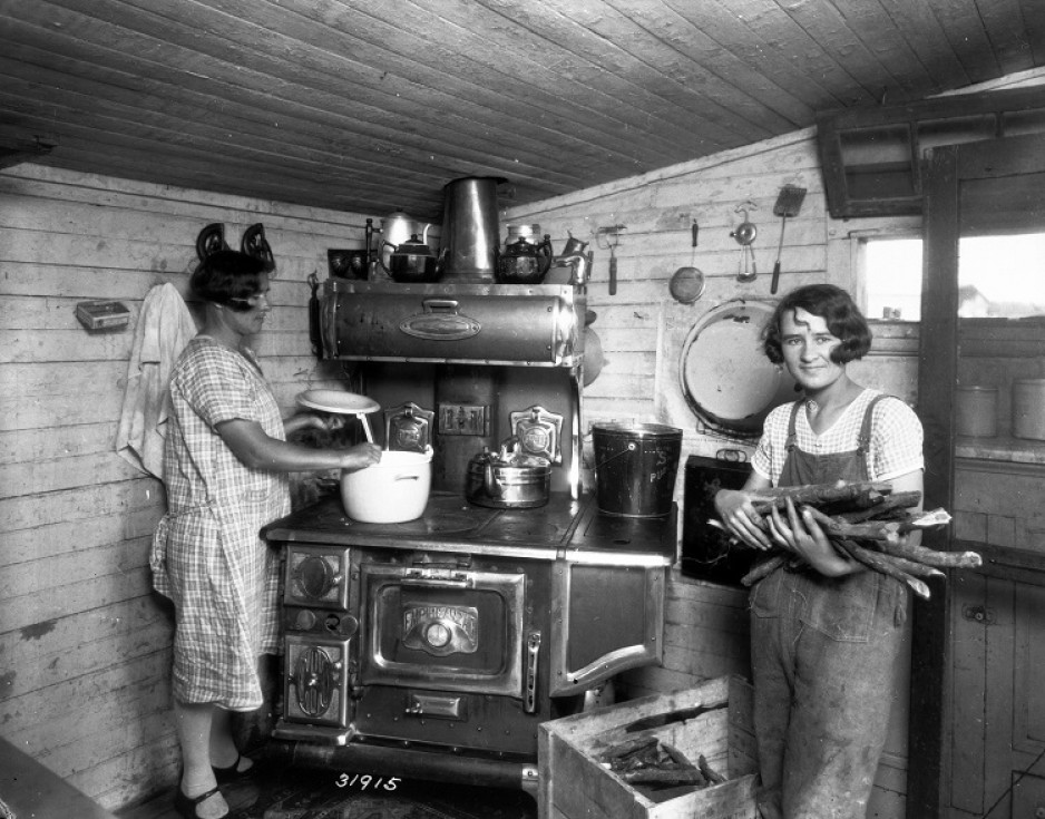 Preparing dinner on a wood stove in the First House, St Jean-Baptiste MB