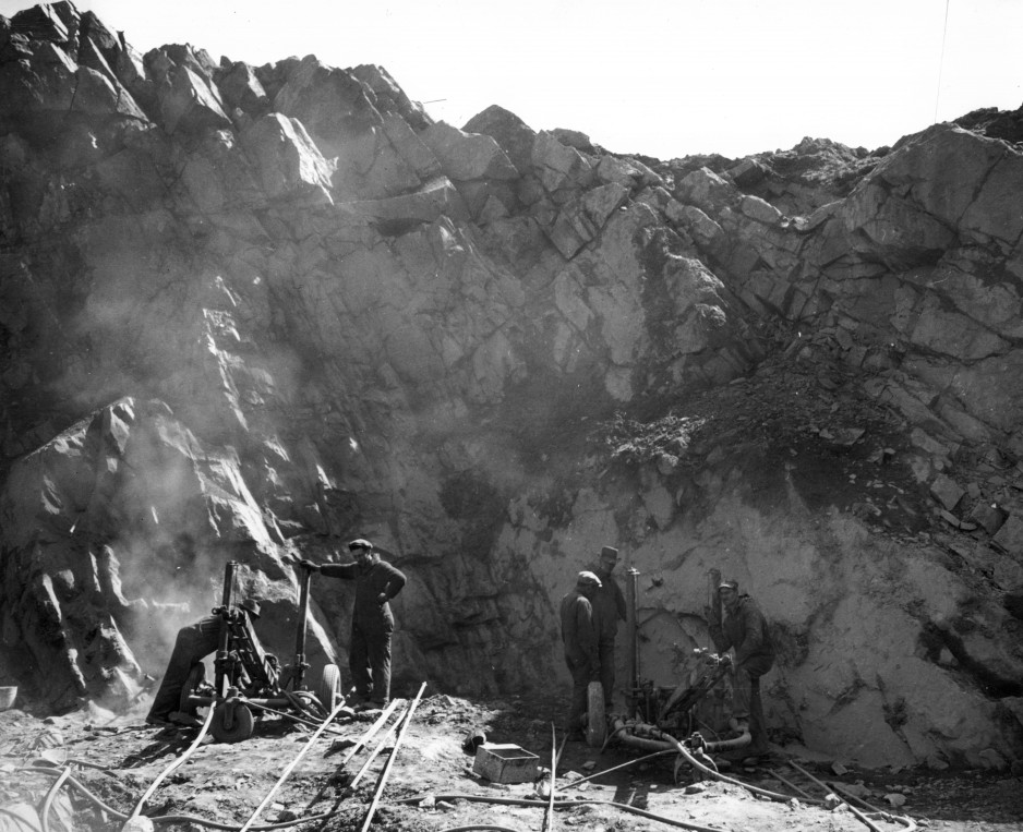 Photograph shows drillers at work on the face of an entire hill of iron ore, Bathurst, New Brunswick, 1943