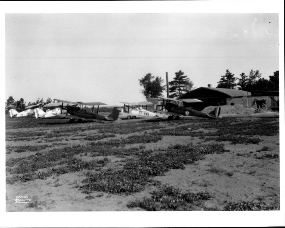 A lineup of period civilian and RCAF aircraft parked in front of an old hangar at Rockcliffe