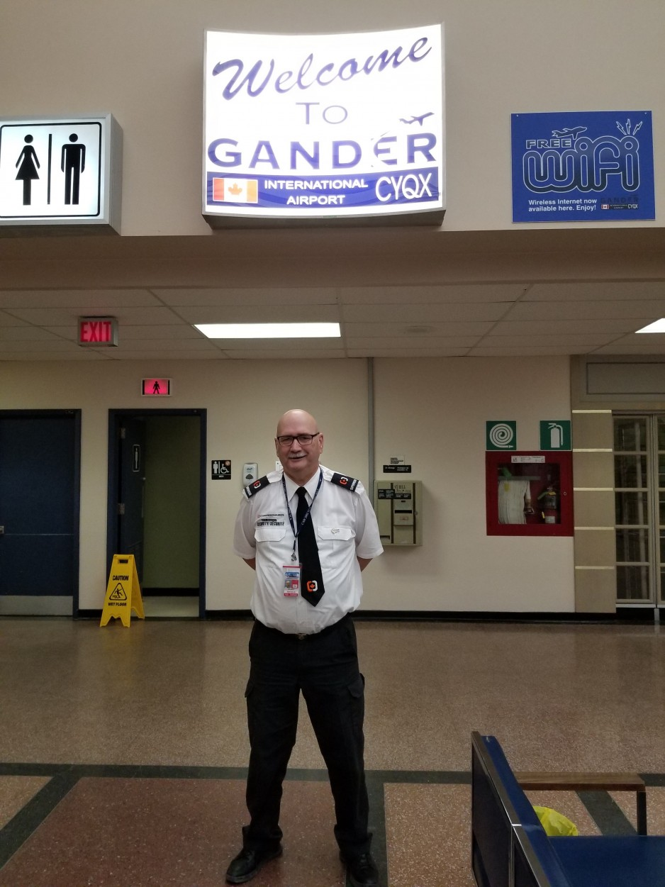 "Our guide Jerry Cramm standing in the international area in front of a ""Welcome to Gander"" sign."
