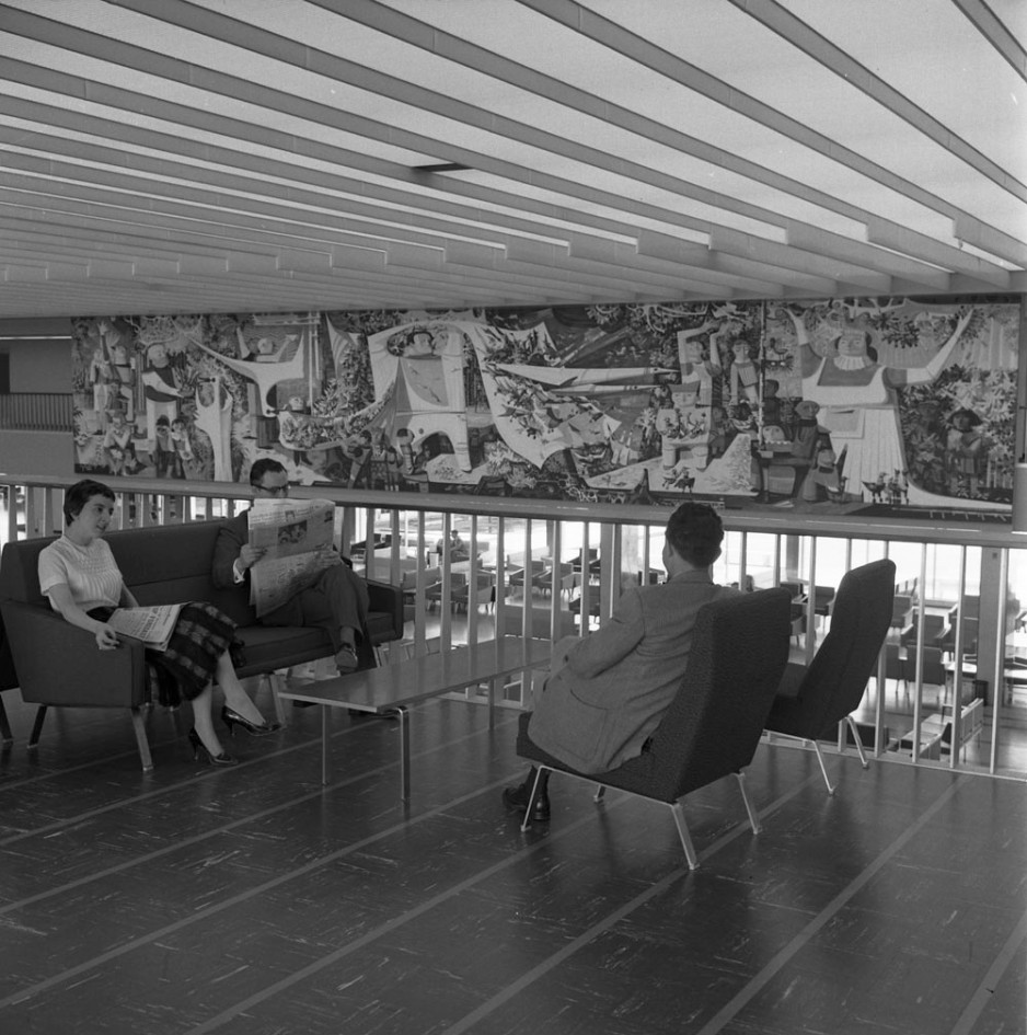 People waiting in the international lounge of the new terminal. Artist Ken Lochhead's impressive mural is visible in the background.