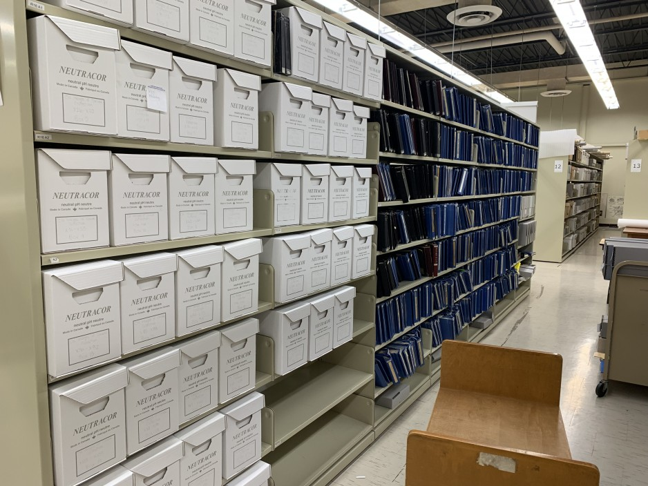 Seven rows of shelving units; the first two sections of shelving have boxes, the next five sections have albums.]