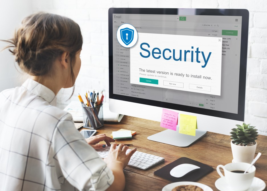 Woman installing cyber security software on a desktop computer