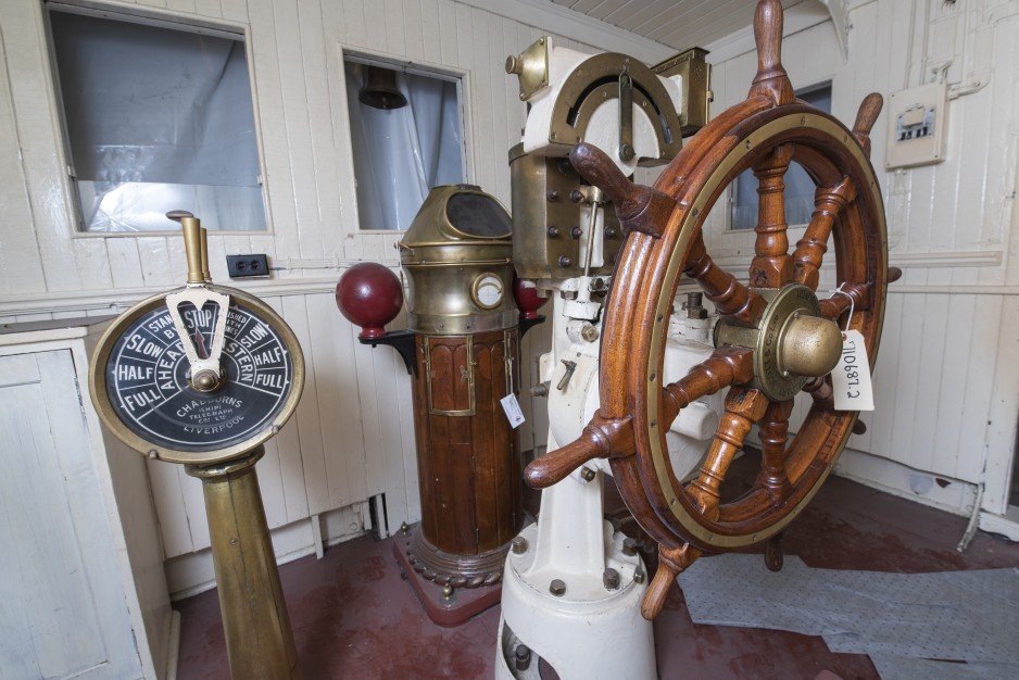 A view of the steering wheel and other pieces of equipment, inside the wood-panelled walls of the pilot house.