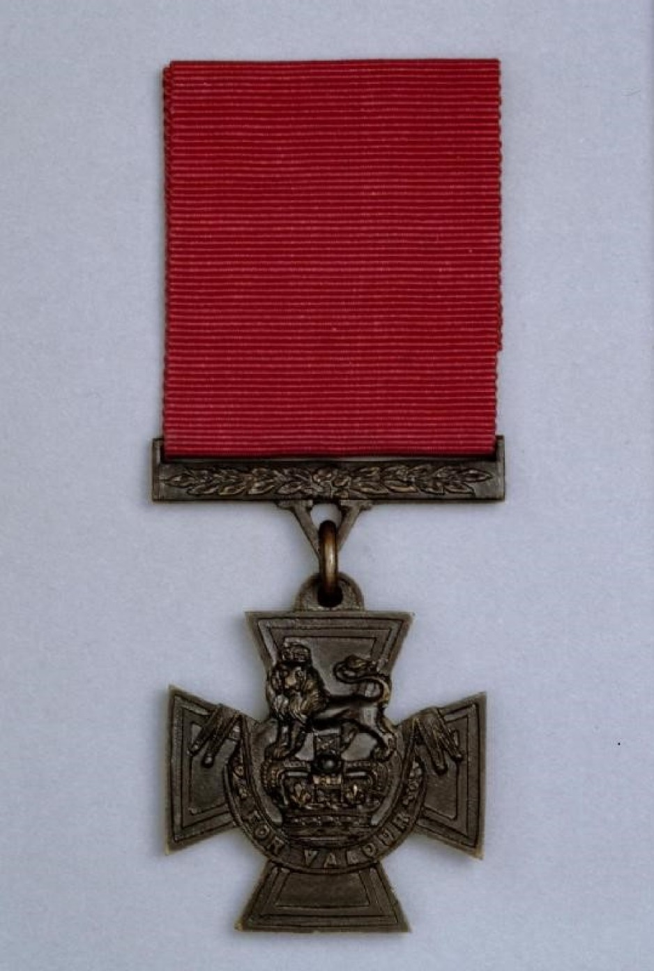 "A Victoria Cross medal — a bronze cross with a lion atop a crown, with the inscription ""For Valour"" across the bottom."