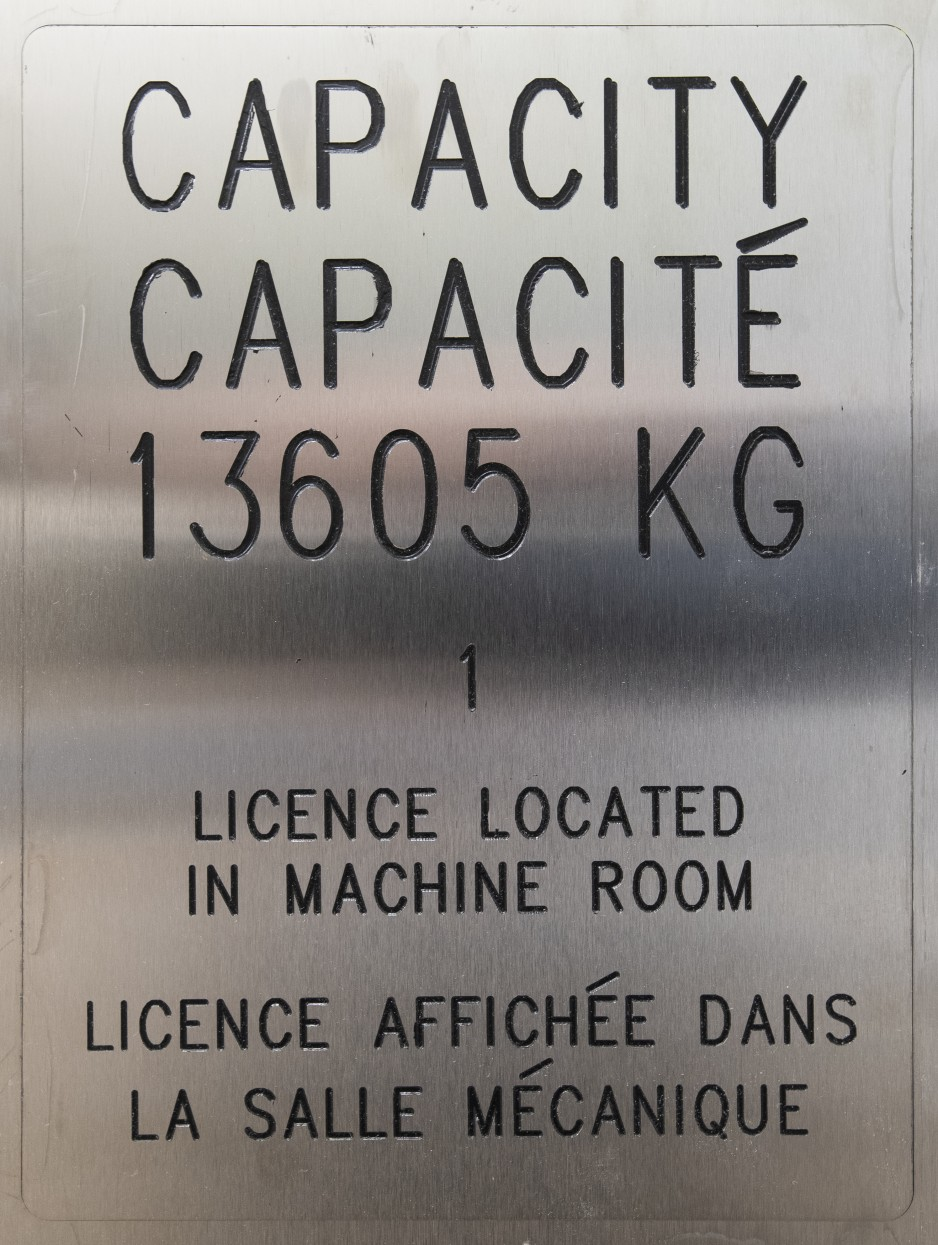 A close-up of a silver panel in the freight elevator indicates the maximum capacity is 13,605 kg.