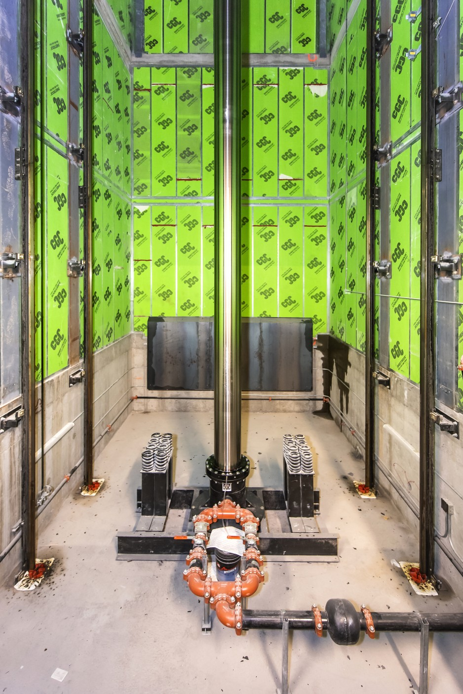 An inside view of the elevator shaft, which is a rectangular enclosure with bright green walls and a massive, steel column in the middle.