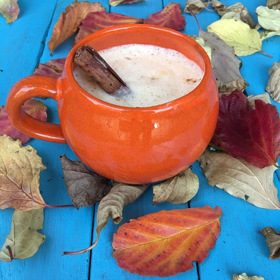 A mug filled with pumpkin spice latte, sitting on an outdoor table surrounded by fall leaves.