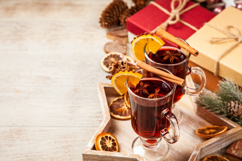 Two decorative glasses of mulled wine sitting on tray next to some presents