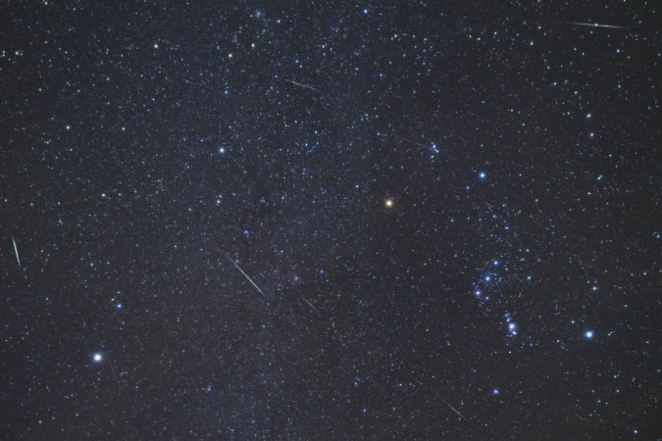 An image of the night sky with the constellation of Orion prominently shown, with multiple meteors streaking across the sky.