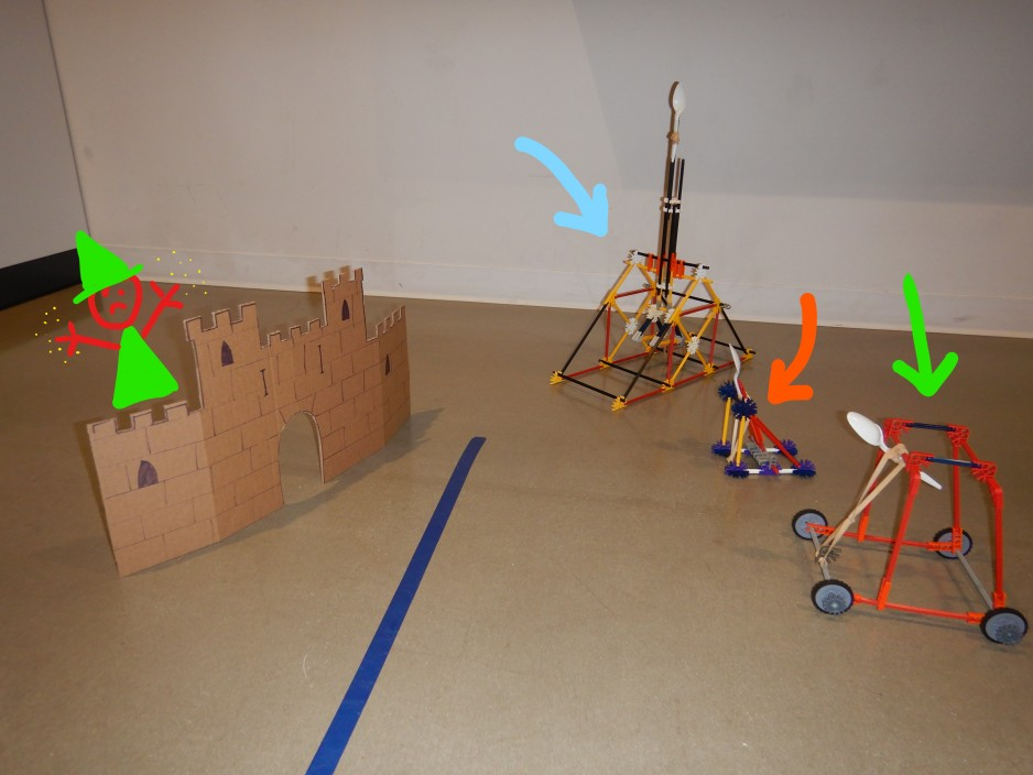A display of several K'NEX catapults lined up next to a cardboard castle target
