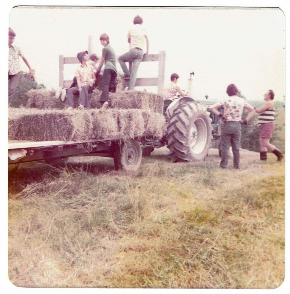 An old photo shows kids taking a tractor-pulled hayride.